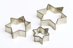 Three star shaped Christmas cookie cutters over white Stock Image
