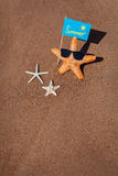 Three starfish and summer flag on the sand Stock Image
