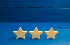 Three stars on a blue background. The concept of rating and evaluation. The rating of the hotel, restaurant, mobile application. Q. Uality service, buyer choice royalty free stock photography