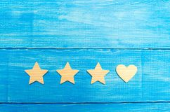 Three stars and a heart on a blue background. Selection of the user and clients. Universal recognition and admiration. Rating of a. Hotel or restaurant stock images