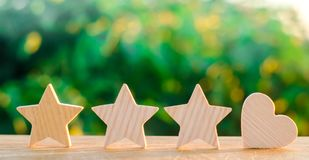 Three stars and heart on a green bokeh background. four star rating, the choice of the editorial office and the buyer. concept of. Rating, review. quality royalty free stock photos