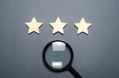 Three stars and a magnifying glass on a gray background. Rating and status of the restaurant or hotel. Prestige. High quality and. Reliability, universal royalty free stock images