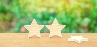 Three stars, a star fell. The concept of a fall in rating and quality. Deprivation of the third star. Feedback on the level. Of services for hotels, restaurants royalty free stock image