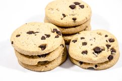 Three stasks of chocolate chip cookies. A cookie is a baked or cooked food that is small, flat and sweet. It usually contains flour, sugar and some type of oil Stock Photo