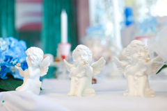 Three statues of angels on the table Stock Photos