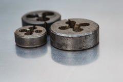 Three steel dies Stock Images