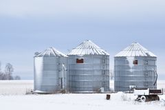 Three steel silos or grain bins covered in snow on a farm in a rural area in winter with a small wagon in the foreground stock photography