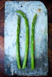 Three stems of fresh green asparagus on a stone board Stock Photo