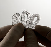 Three stents for endovascular surgery. Surgeon's hand holding self-expanding nitinol stents for endovascular surgery for comparison Stock Image