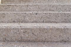 Three steps of a grey concrete staircase taken from the front royalty free stock image