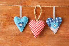 Three stitched red hearts made of cloth hanging on a clothesline Stock Image