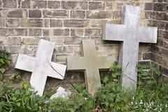 Three Stone crosses. Three stone cross head stones against wall stock image