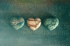 Three stone hearts on wood Stock Photos