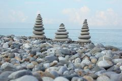Three stone stacks on pebble beach Stock Photos