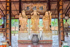 Three stone statues bearing symbol `Blessing, fortune, expectancy`. Long An, Vietnam - September 18th, 2016: Three stone statues bearing symbol `Blessing Stock Images