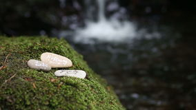 Three stones with german words for love, hope and faith in front of waterfall