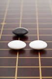 Three stones during go game playing. On wooden board close up Royalty Free Stock Photos
