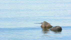 Three stones laying in a calm ocean in shallow water Royalty Free Stock Image