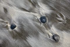Three stones on sand Stock Image