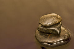 Three Stones In Still Water Background Royalty Free Stock Photos