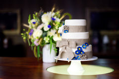 Three stories wedding cake decorated with blue flowers Royalty Free Stock Images