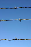 Three strands of barbed wire. Three strands of barbed wire in front of a great blue sky Stock Photography
