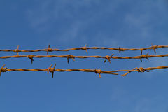 Three strands of rusty barbed wire against the sky Stock Photo