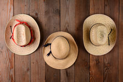 Three Straw Hats. Hanging on a rustic wood farmhouse wall. Closeup in horizontal format Stock Photo