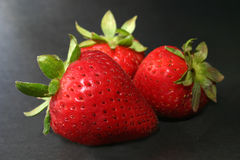 Three strawberries. Threes strawberries on dark background Royalty Free Stock Photo