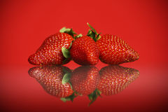 Three strawberries against red background Stock Photo