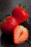 Three strawberries on black with water drops Stock Photo