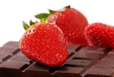 Three strawberries and chocolate. Stock Image