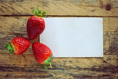 Three strawberries and empty paper blank Stock Photo