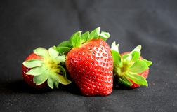 Three strawberries lying/standing on black fabric royalty free stock images