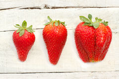 Three  strawberries over white wood Royalty Free Stock Photography