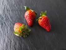 Three strawberries on slate Royalty Free Stock Images