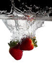Three strawberries in water. Three strawberries falls in water royalty free stock images
