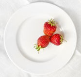 Three strawberries on a white plate. 3 strawberries lying in a form of triangle on a white plate with background made of linen tablecloth Stock Photo