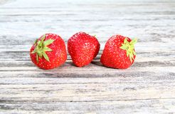 Three strawberries on a wooden table Stock Photography