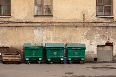 Three street dustbins. Three street green garbage can with wheels and folding lids. Near ragged wall royalty free stock photos
