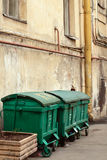 Three street dustbins. Three street green garbage can with wheels and folding lids. Near ragged wall stock photos