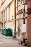 Three street dustbins. Three street green garbage can with wheels and folding lids. Near ragged wall stock photography