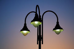 Three street lights at dusk. Three street lights in a city park Royalty Free Stock Images