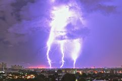 Three strikes ... Electrical storm showing three lightening bolts hitting earth over a night time townscape royalty free stock photos