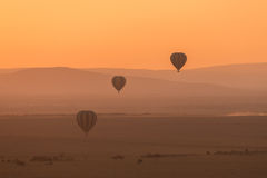 Three striped balloons fly over purple hills Royalty Free Stock Photos