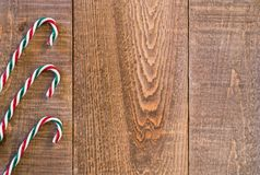 Three striped candy canes along left border of rustic wooden sur Royalty Free Stock Photo