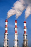 Three striped industrial pipes with smoke over cloudless blue sky Stock Photography
