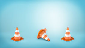 Three striped traffic cones placed on blue background and the middle one lying on its side. Royalty Free Stock Images