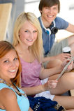 Three student friends with tablet smiling camera Stock Photo