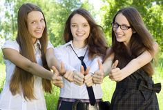 Three student girl with thumbs-up in the park. Three happy student girl with thumbs-up in the park Stock Photo